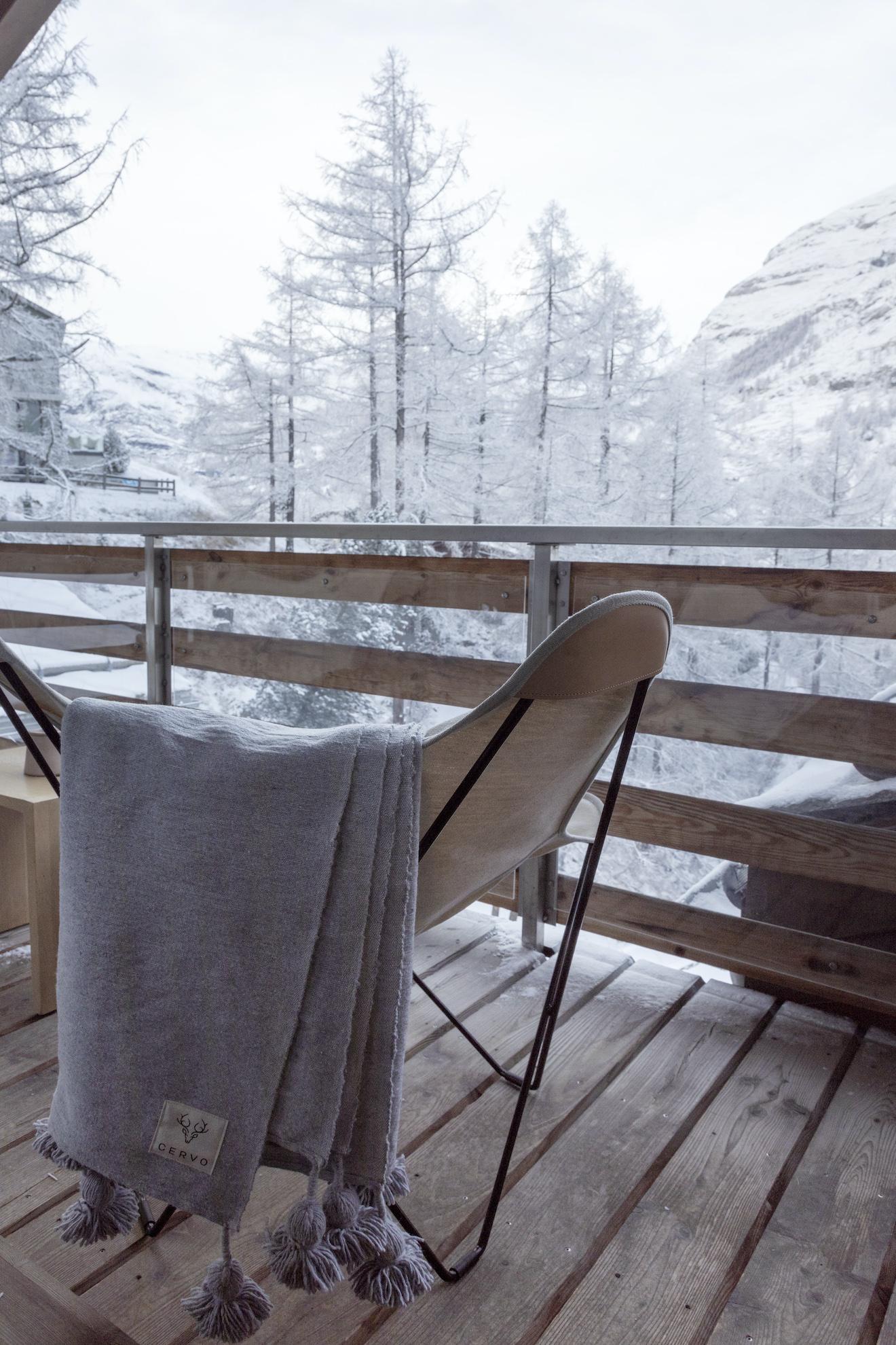 Balkon im Winter mit Stuhl und Decke